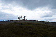 Three walkers stand at the end of the trail path on Blencathra Mountain, Lake Districts, Cumbria, UK.  The sky is full of clouds and overcast.  (photo by Andrew Aitchison / In pictures via Getty Images)