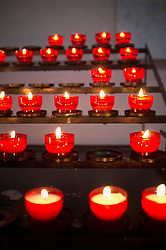 Row red prayer candles burning line flame church