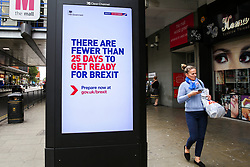 © Licensed to London News Pictures. 10/10/2019. London, UK.A woman walk past a digital billboard featuring the UK government's latest 'Get Ready for Brexit' advertising campaign in Wood Green Shopping Mall, north London, with twenty one days to Brexit day. The 'Get Ready for Brexit' campaign is costing the UK government £100m. Photo credit: Dinendra Haria/LNP