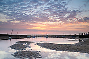 Dawn reflections at low tide, Burnham Overy Staithe, rumoured to be the harbour in which Horatio Nelson learnt to sail. North Norfolk, East Anglia.