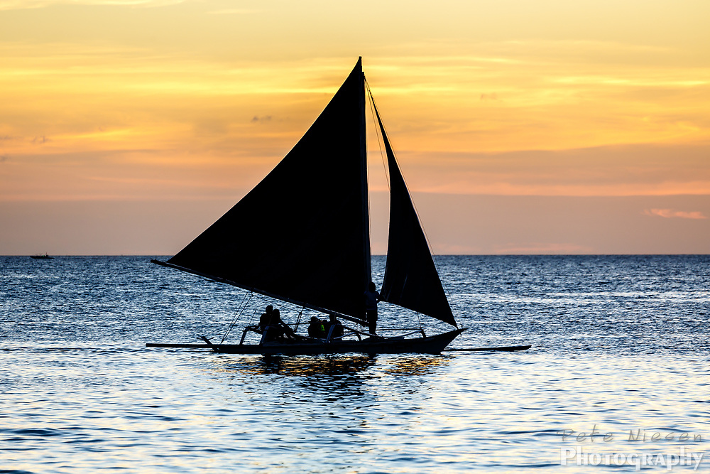 Silhouette of people sailing outrigger sailboat at sunset