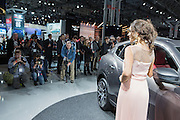 New York, NY, USA-23 March 2016. A model pses beside a Maserati Levante, the automaker's first foray into the luxury SUV market. The surrounding photographers were paying more attention to the model than to the car.
