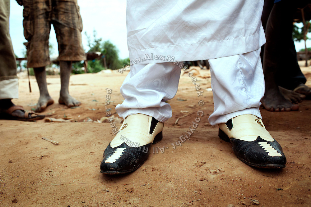 The chairman of a large artisanal gold processing site near Bagega, pop. 9000, Zamfara State, Nigeria, is exhibiting classy shoes while standing among his workers. The lead contamination is caused by ingestion and breathing of particles released in the steps to isolate the gold from other metals. This type of lead is soluble in stomach acid and children under-5 are most affected, as they tend to ingest more through their hands by touching the ground, and are developing symptoms often leading to death or serious disabilities.