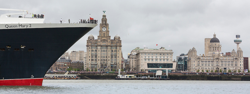 Cunard Lines' Queen Mary 2 passes the Royal Liver Building (left), the Cunard Building and the Pourt of Liverpool Building (right) as their fleet gather together in spectacular fashion in Liverpool, its spiritual home, as the company marked its 175th anniversary. The historic lines' three ships, the largest passenger ships ever to muster together on the River Mersey, lined up just 130 metres apart in the river.<br /> Picture date Monday 25th May, 2015.<br /> Picture by Christopher Ison. Contact +447544 044177 chris@christopherison.com