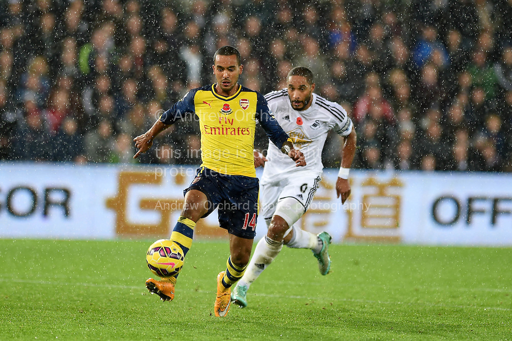 Arsenal's Theo Walcott goes past Ashley Williams of Swansea city.  Barclays Premier league match, Swansea city v Arsenal at the Liberty Stadium in Swansea,  South Wales on Sunday 9th November 2014. <br /> pic by Andrew Orchard, Andrew Orchard sports photography.