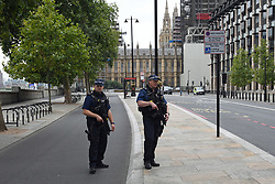 Armed police on Victoria Embankment in Westminster, central London, after a car crashed into security barriers outside the Houses of Parliament.