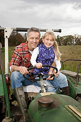 Farmer with daughter on tractor
