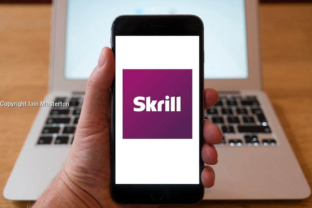 Using iPhone smart phone to display website logo of Skrill e-commerce business for money transfer