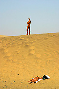 A nude man stands on top of a sand dune and a nude woman tans herself at Maspalomas beach, Gran Canaria, Canary Islands, Spain.
