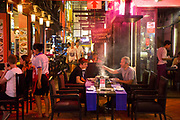 Diners sit outside eating in restaurants on Pub Street in downtown Siem Reap, Cambodia, Asia. Siem Reap is the capital city of the Siem Reap Province.  Pub Street is a famous destination for lively nightlife for tourist and travellers as it restaurants and bars stay open late.