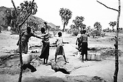 """NUBA MOUNTAINS, SUDAN – JUNE 9, 2018: Nuba women gather water from a shallow well. <br /> <br /> In 2011, the government of Sudan expelled all humanitarian groups from the country's Nuba Mountains. Since then, the Antonov aircraft has terrorized the Nuba people, dropping more than 4,080 bombs on hospitals, schools, marketplaces and churches. Today, vestiges of the Antonov riddle the landscapes of daily life, where more than 1 million Nuba live in famine conditions – quietly enduring the humanitarian blockade intended to drive them out of the region. The skies are mostly clear. Yet the collective memory of the bombings remains an open wound, and the Antonov itself a persistent threat. So frequent were the attacks that the Nuba nicknamed the high flying aircraft and its dismal hum: """"Gafal-nia ja,"""" they would declare, running to the hillsides. """"The loss of appetite has come."""""""