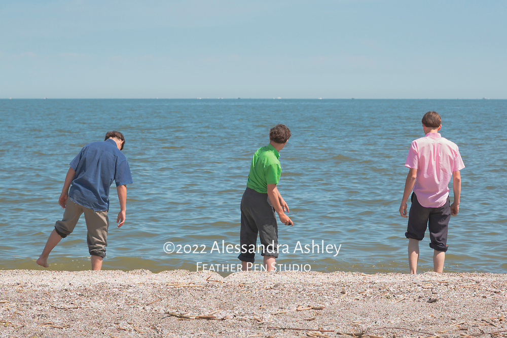 Three Amish boys in traditional clothing at edge of Lake Erie in late May.