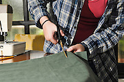 Young female teen of fifteen sewing cutting the fabric Model release available