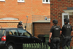 © licensed to London News Pictures. Norwich, UK  06/05/2011. At least six police cars are at the house in Badger Road, on the Hampdens development near Longwater Lane. The police helicopter is also circling overhead.A woman, believed to be the hostage, appeared at the window of the house at 12:25pm and spoke to police for five minutes..The curtains of the house have remained drawn and the front room has newspapers covering the window. There is believed to be a man and woman inside. There are five armed policemen standing guard at the front of the house, with guns trained on the house, and two or three more at the back, as well as other officers blocking the road further down.. Please see special instructions for usage rates. Photo credit should read Alan Bennett/LNP