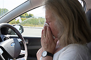 As the first part of a Coronavirus test, a middle-aged lady blows her nose from the driver's seat of her car before a self-administered Coronavirus (COVID-19) test in south London. There are four steps (inserting a swab into the nose and throat) to the self-administered Covid-19 test which the public works through in their car, windows up and all communications with army personnel via phone, in a south London leisure centre, on 2nd June 2020, in London, England. The kit provided consists of a booklet, plastic bag, swab, vial, bar codes and a sealable biohazard bag. The swab sample is taken from the back of the throat and nasal passage with the contents sealed and returned to soldiers through a narrow window. The whole process takes between 5-10mins with results available with 48hrs.