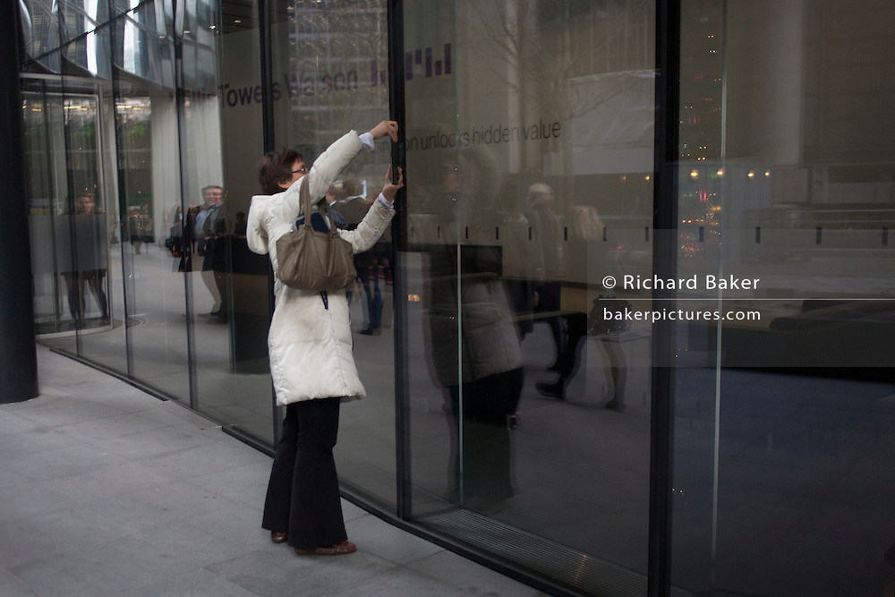 A woman uses her smartphone to photograph a corporate foyer interior, her phone seemingly blended with the building's architecture, on 9th December 2016, in the City of London.