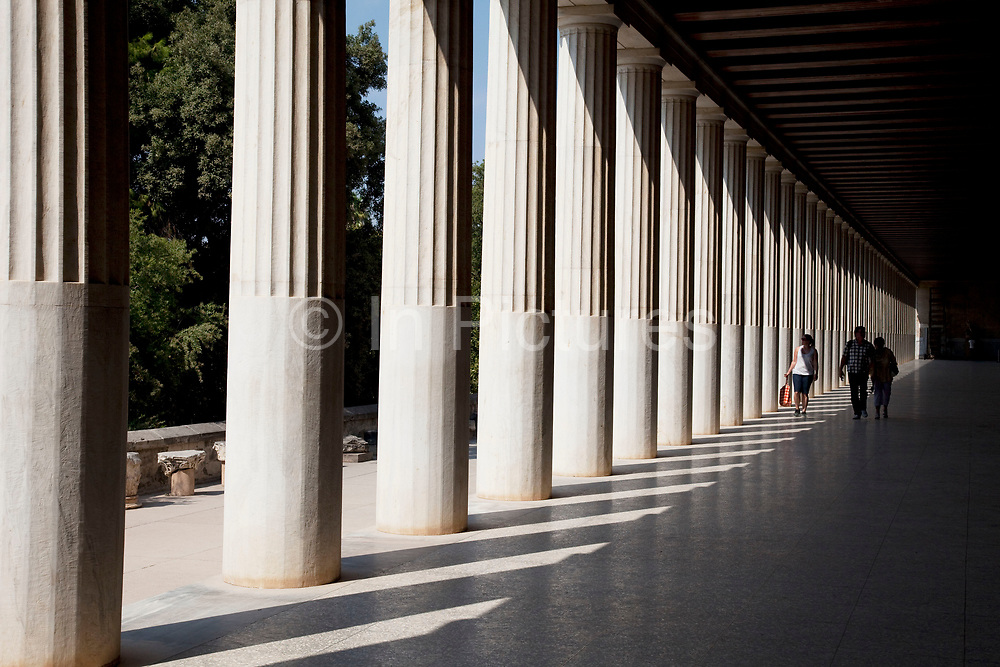 Tourists at The Stoa of Attalos or Attalus located in the east side of archaeological site of the Ancient Agora in Athens just oposite the Adrianou street in Monastiraki. The Stoa of Attalos was built around 150 BC, by Attalos II, King of Pergamos as a donation to Athens. The construction of the building began in 159 BC and ended in 138 BC. The building was the largest in length in Greece during the antiquity. It was rebuilt in the same style and shape from 1953 to 1956 with beautifully crafted marble columns. It is recognised as one of the most impressive stoa in the Athenian Agora. Typical of the Hellenistic age, the stoa was more elaborate and larger than the earlier buildings of ancient Athens. The stoa's dimensions are 115 by 20 metres wide (377 by 65 feet wide) and it is made of Pentelic marble and limestone. The building skillfully makes use of different architectural orders. The Doric order was used for the exterior colonnade on the ground floor with Ionic for the interior colonnade. Athens is the capital and largest city of Greece. It dominates the Attica periphery and is one of the world's oldest cities, as its recorded history spans around 3,400 years. Classical Athens was a powerful city-state. A centre for the arts, learning and philosophy.
