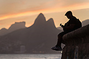 A man plays guitar on the seawall at Ipanema beach silhouetted by sunset with the Two Brother mountains in the distance in Rio de Janeiro, Brazil.
