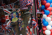 Mother and child with patriotic bunting, flags, balloons and royal memorabilia on display before the Queen's diamond Jubilee in a south London shop window.