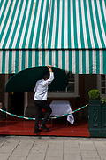 A waiter carries a semi-circular half table outside a Mayfair restaurant. Struggling under the weight and awkward nature of the large shape, the worker makes his way along the pavement with hands grabbing each edge to place it with the other half, in a space beneath the green and white awning - ready for lunchtime trade.