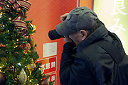 elderly man photographing the decoration on a christmas tree Japan