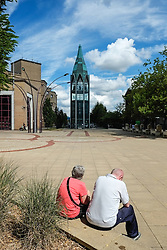 Two people sit in St Martins Square in Basildon Town Centre. Essex