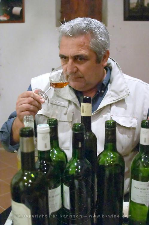 Jean-Louis Poudou with lots of bottles. Domaine La Tour Boisee. In Laure-Minervois. Minervois. Languedoc. Owner winemaker. Tasting wine. France. Europe. Bottle.