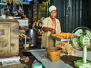 04 JANUARY 2016 - BANGKOK, THAILAND:        A baker in Bang Chak Market pulls his last batch of Thai cakes out of the oven in Bang Chak Market on the day the market closed. The market closed January 4, 2016. The Bang Chak Market serves the community around Sois 91-97 on Sukhumvit Road in the Bangkok suburbs. About half of the market has been torn down. Bangkok city authorities put up notices in late November that the market would be closed by January 1, 2016 and redevelopment would start shortly after that. Market vendors said condominiums are being built on the land.   PHOTO BY JACK KURTZ