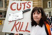Fourth 48 hour strike by junior doctors over proposed changes to their contracts with the NHS on Westminster April 6th 2016 in Westminster, London, United Kingdom. Gill Thompson holds a placard with a chopper on it and the words 'Cuts kill' Her brother David Clapson died after welfare sanctions left him penniless.