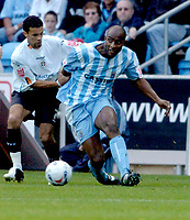Photo: Leigh Quinnell.<br /> Coventry City v Luton Town. Coca Cola Championship.<br /> 29/10/2005. Coventrys Dele Adebola shakes off Lutons Carlos Edwards to make the pass.