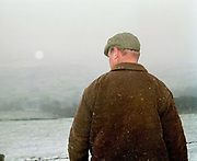 The back of gamekeeper Don Herd as he looks towards Ruscoe Farm in the snow, Upper Nidderdale, North Yorkshire, UK