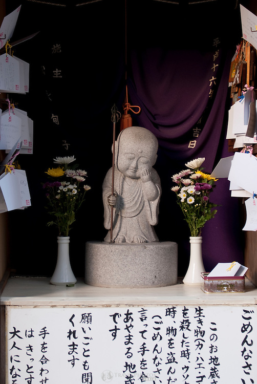 A small Buddha statue on the side of a road in Imaike, Nagoya.