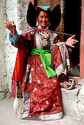 INDIA, LADAKH Portrait of a Tibetan woman wearing traditional dress and turquoise jewelry spinning wool