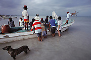 Throwing out the anchor on a small fishing boat on the beach at Campeche, Mexico.