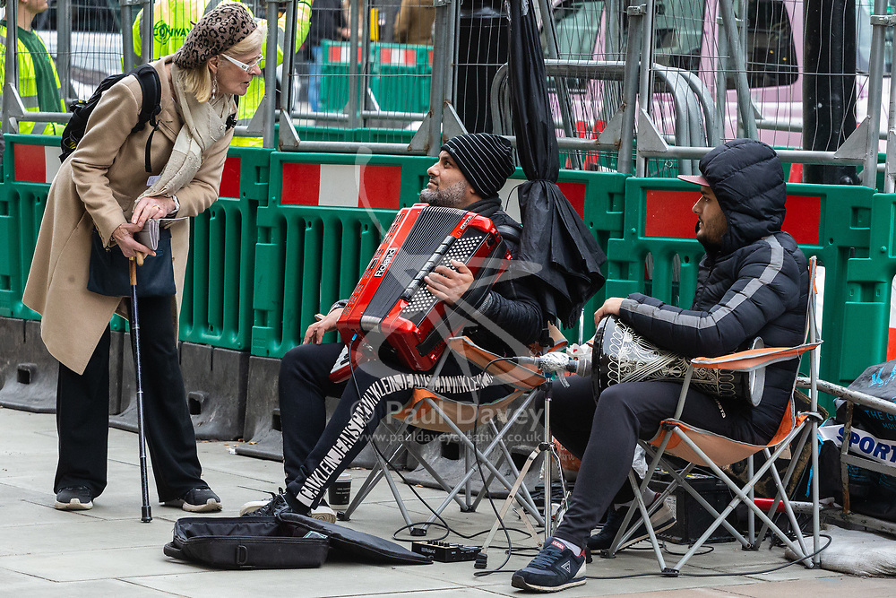 A woman chats to two Romanian street musicians on Oxford Street. Homeless Britons are coming under increasing pressure as a surge of Roma beggars from Romania arrive on the streets of London to take advantage of the generosity of Christmas shoppers. London, December 04 2018.