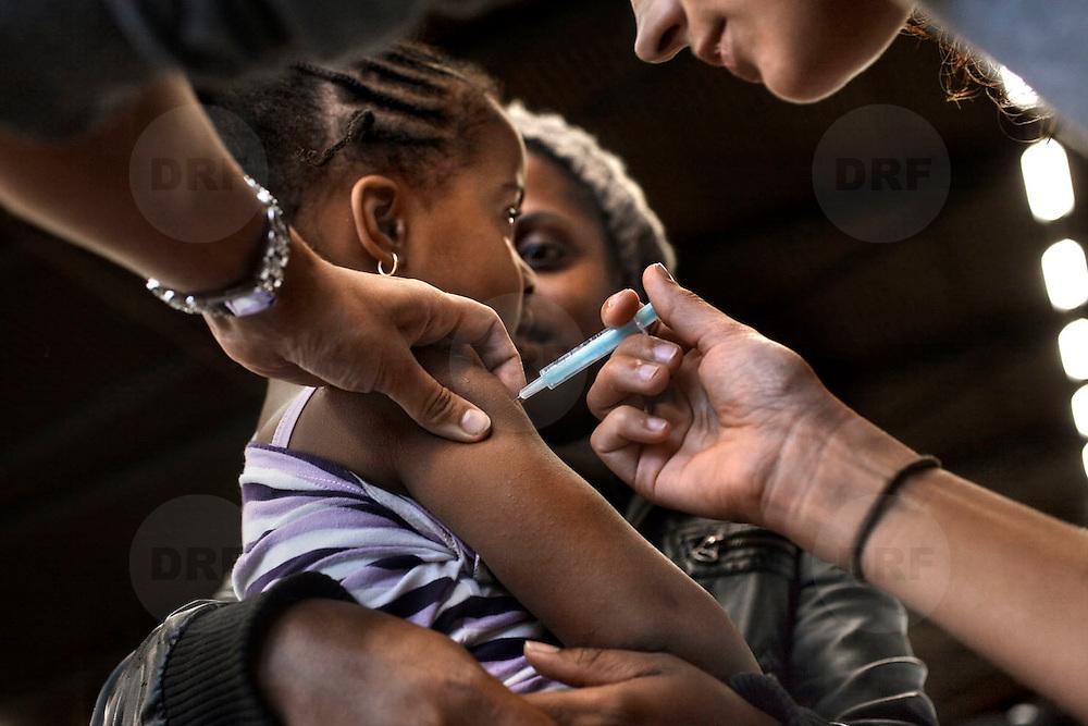 Nederland Rotterdam 26-11-2009 20091126 Foto: David Rozing                        Massa vaccinatie GGD tegen de Mexicaanse Griep in evenementenhal Ahoy Rotterdam. Meisje op schoot van haar moeder krijgt het vaccin toegedient/ vaccinatieprik. Deze vaccinatie is de grootste in de geschiedenis van Nederland, in totaal zijn bijna 44.000 kinderen van een halfjaar tot vijf jaar en huisgenoten van kinderen jonger dan een half jaar opgeroepen om naar Ahoy te komen voor een vaccinatie tegen de Mexicaanse griep. Ook huisgenoten van kinderen tot 6 maanden kunnen een prik krijgen.  De vaccinatie tegen de Mexicaanse griep bestaat uit twee prikken. Het halen van beide prikken is belangrijk om voldoende bescherming te krijgen.  Dutch officials started mass vaccination campaign  a mass immunization by offering vaccin in stadion/ sportcentre Ahoy. Holland's health authority stepped up a mass vaccination campaign and other measures to combat swine flu. ..Holland, The Netherlands, dutch, Pays Bas, Europe ..Foto: David Rozing