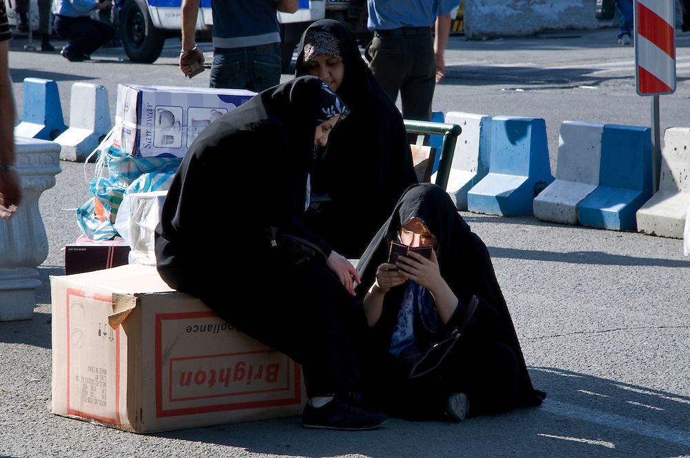 Young women at Teheran's souk waiting for a car.