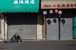 An intoxicated man crawls on the street in Kamagasaki, Japan.