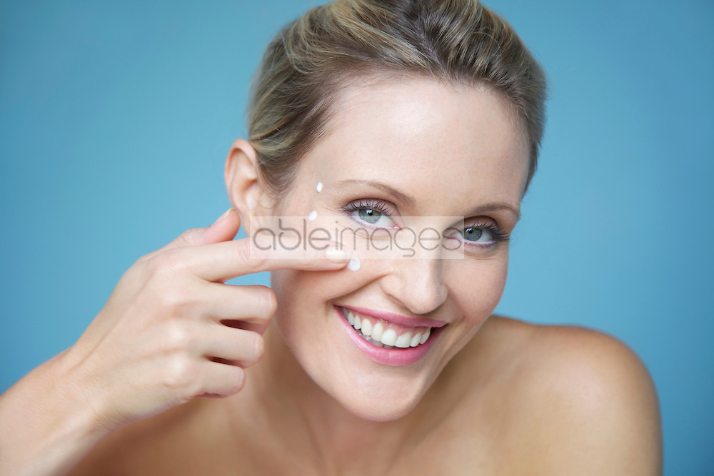 Smiling Woman Applying Moisturizing Cream on her Face