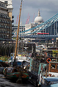 With the dome of St Pauls Cathedral the south suspension chains of Tower Bridge in the distance, privately-owned boats of many kinds sit in the low-tide mud on the Thames river at the a river community Tower Bridge Moorings, on 14th September 2017, in London, England.