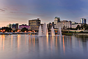 Downtown skyline reflected in Lake Lucerne at twilight in Orlando, Florida.