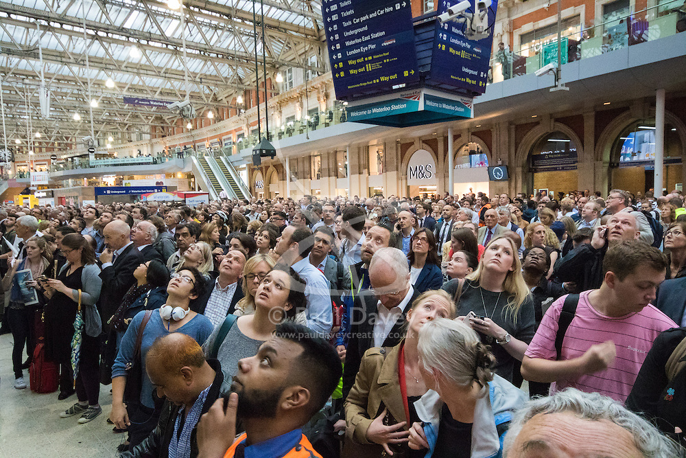 Waterloo Station, London, June 23rd 2016. Commuters face severe delays at London's Waterloo Station as bad weather causes power failures across the rail network. PICTURED: Faces peer anxiously at the departure screens, most of which show cancelled or delayed services.