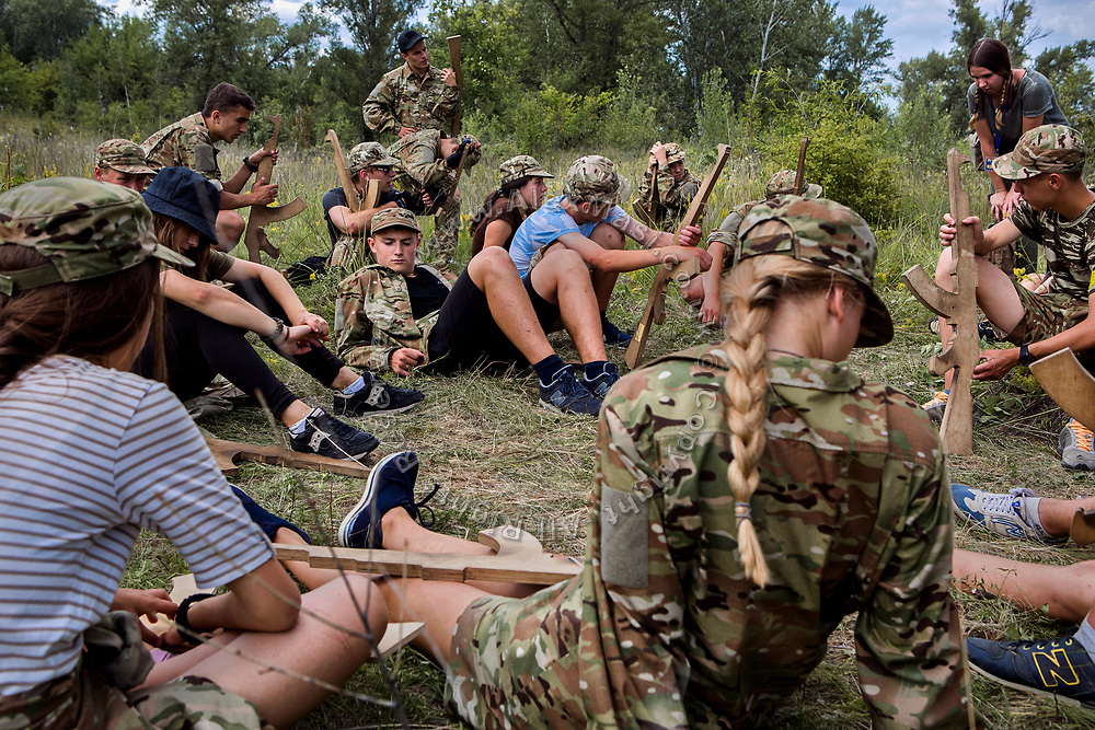 Youngsters participating to the ultra-nationalistic Azovets children's camp are taking a break to relax on the grass, during tactical training on the banks of the Dnieper river, in Kiev, Ukraine's capital.