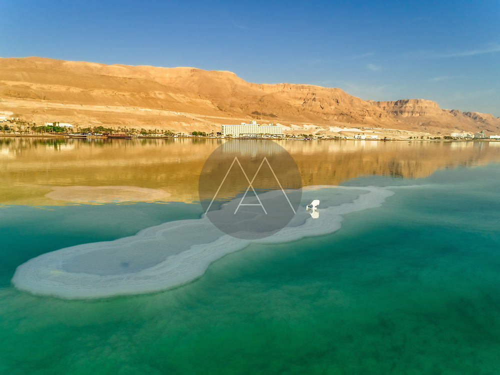 Aerial view of a plastic chair in the colourful water of dead sea and mountains and hotels in the horizon, Dead sea, Negev, Israel.