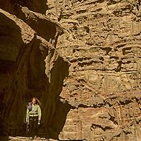 A rock climber approaches remote desert cliffs in Rakabat Siq (canyon), on (mount) Jebel Um Ishrin, Wadi Rum, Jordan.