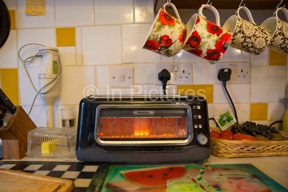 Bread being toasted in a SilverCrest toaster with a glass front in a kitchen in Bethesda, Gwynedd, Wales.