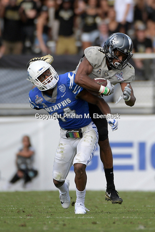 Central Florida wide receiver Tre'Quan Smith (4) catches a pass over Memphis defensive back Jonathan Cook (14) during the first half of the American Athletic Conference championship NCAA college football game Saturday, Dec. 2, 2017, in Orlando, Fla. (Photo by Phelan M. Ebenhack)