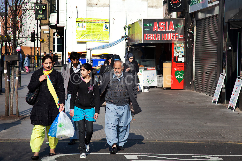 A family pass the Asia Kebab House in Southall in West London, also known as 'Little India' by some, is an area almost completely populated by people from South Asia. Figures show that the area is approximately 50 percent Indian in origin although walking the streets it would appear far higher as the local people go about their shopping in the many shops specialising in goods specific to this culture. The mix of religions is mainly Sikh, Hindu and Muslim.<br /> <br /> Southall is primarily a South Asian residential district. 1950 was when the first group of South Asians arrived in Southall, reputedly recruited to work in a local factory owned by a former British Indian Army officer. This South Asian population grew due to the closeness of expanding employment opportunities. The most significant cultural group to settle in Southall are Indian Punjabis.