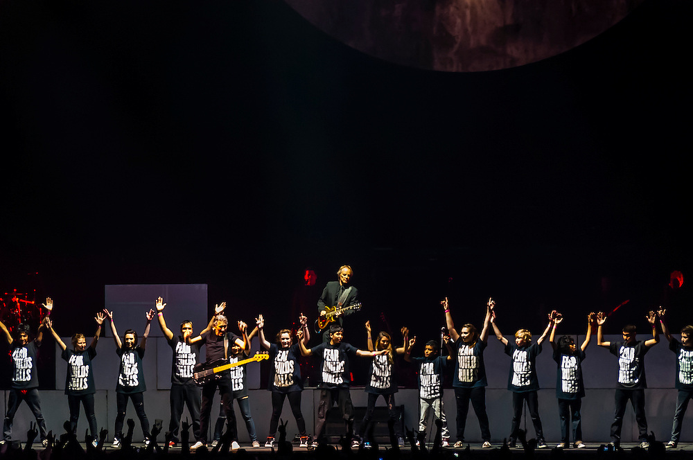 """A children's choir performs """"Another Brick in the Wall, Part 2"""" with Roger Waters, a founding member and former bass player and lead vocalist of Pink Floyd, performs The Wall Live (an audio visual specatacle including 3D Animation and pyrotechnics) at the Pepsi Center, Denver, Colorado USA"""
