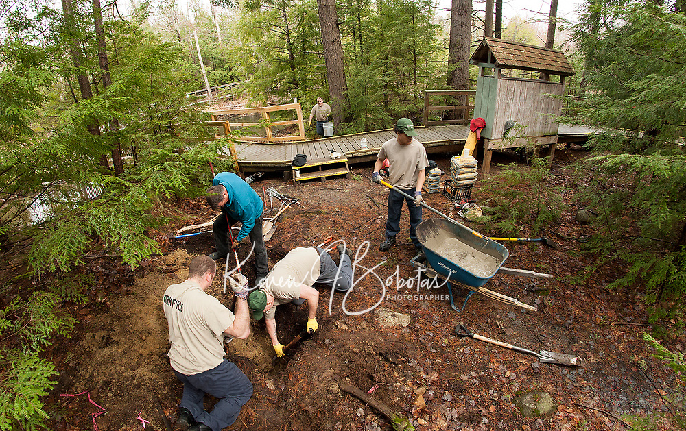 Eric Gonyer, Chris Krupp, Mark Monsantee, Robert Guidi and Jordan Smith prepare the site for a bike rack station at the entrance of the Wetland's Walk at Gunstock Resort during Laconia Rotary's volunteer service project.  (Karen Bobotas/for the Laconia Daily Sun)